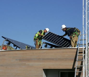 Team Boston advisors Robert Darnell, center, and Pete MacDougall set a photovoltaic panel on the roof of their team's house during the 2009 U.S. Department of Energy Solar Decathlon on the National Mall in Washington, D.C., Monday, Oct. 05, 2009. (Photo by Stefano Paltera/US Dept. of Energy Solar Decathlon)